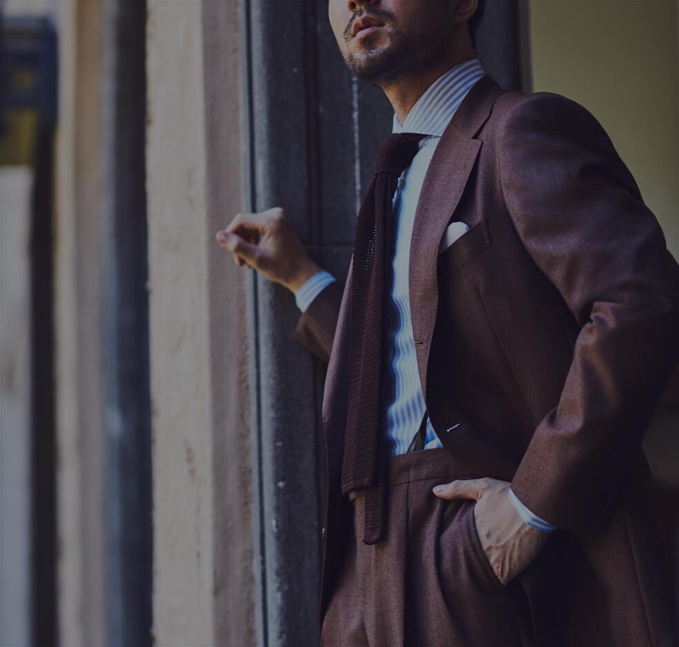 ビジネスシーンで着用する、紳士のスーツスタイルをご紹介。THE G'S HIDEOUT.(ザ・ジーズ・ハイドアウト)のブラウンのスーツは衿幅が広く、着丈はノーベントとクラシックなディテールになっております。パンツは2タックでエレガントなシルエットを演出します。Vゾーンは、ブルーのストライプのシャツにブラウンのニットタイをコーディネートする事で春夏シーズンのスタイリングになっております。コーディネートで使用しているネクタイブランドはAtto vannucci(アットヴァン ヌッチ)というイタリアで生産を行うブランドで、セッテピエゲという7つ折りのハンドメイドで形成する事が特徴です。シャツは、イタリアブランドBORRIELLO(ボリエッロ)を合わせており、THE G'S HIDEOUT.(ザ・ジーズ・ハイドアウト)ではオーダーいただく事が出来ます。 BORRIELLO(ボリエッロ)のシャツの襟型はTHE G'S HIDEOUT.(ザ・ジーズ・ハイドアウト)オリジナルでエクスクルーシブ仕様になっておりますの、世界に1つのシャツをお作りいただけます。東京の表参道と大阪の心斎橋に展開するTHE G'S HIDEOUT.(ザ・ジーズ・ハイドアウト)にてご来店をお待ちしております。