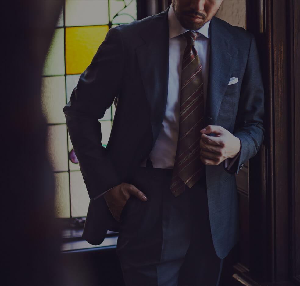 ビジネスシーンで着用する、紳士のスーツスタイルをご紹介。THE G'S HIDEOUT.(ザ・ジーズ・ハイドアウト)のグレイのスーツは衿幅が広く、着丈はノーベントとクラシックなディテールになっております。パンツは2タックでエレガントなシルエットを演出します。Vゾーンは、ホワイトの無地のシャツにグリーンベースのストライプ柄のタイをコーディネートする事で秋冬シーズンのスタイリングになっております。コーディネートで使用しているネクタイブランドはAtto vannucci(アットヴァン ヌッチ)というイタリアで生産を行うブランドで、セッテピエゲという7つ折りのハンドメイドで形成する事が特徴です。シャツは、イタリアブランドBORRIELLO(ボリエッロ)を合わせており、THE G'S HIDEOUT.(ザ・ジーズ・ハイドアウト)ではオーダーいただく事が出来ます。 BORRIELLO(ボリエッロ)のシャツの襟型はTHE G'S HIDEOUT.(ザ・ジーズ・ハイドアウト)オリジナルでエクスクルーシブ仕様になっておりますの、世界に1つのシャツをお作りいただけます。東京の表参道と大阪の心斎橋に展開するTHE G'S HIDEOUT.(ザ・ジーズ・ハイドアウト)にてご来店をお待ちしております。