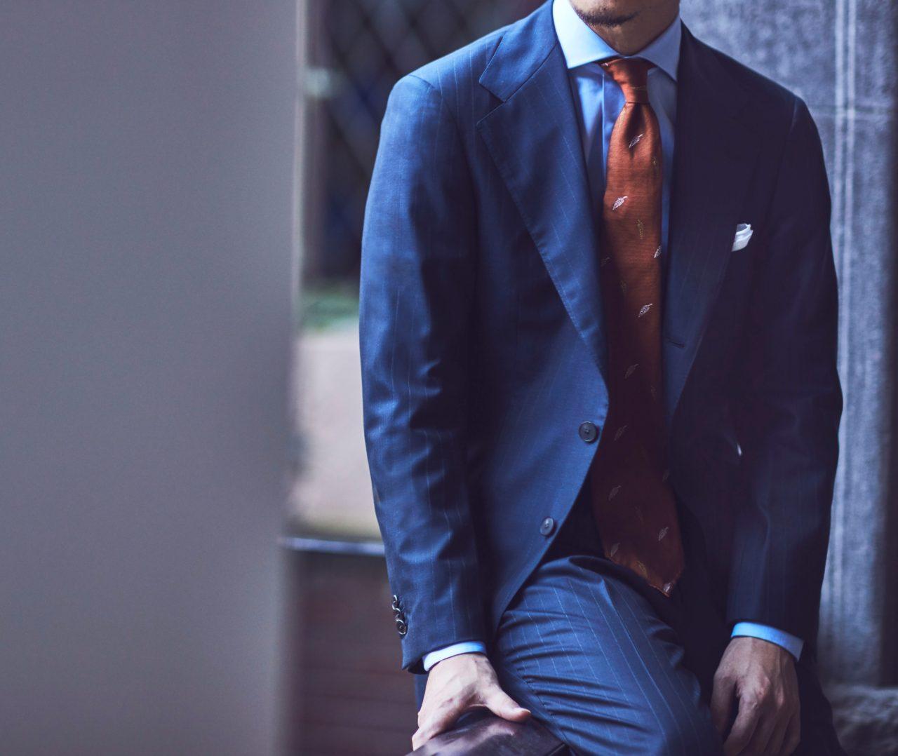 アット ヴァンヌッチ(Atto Vannucci)のオレンジのセッテピエゲネクタイをザ・ジーズ・ハイドアウト(THE G'S HIDEOUT.)のネイビーのオーダースーツに合わせたスタイルのご紹介。