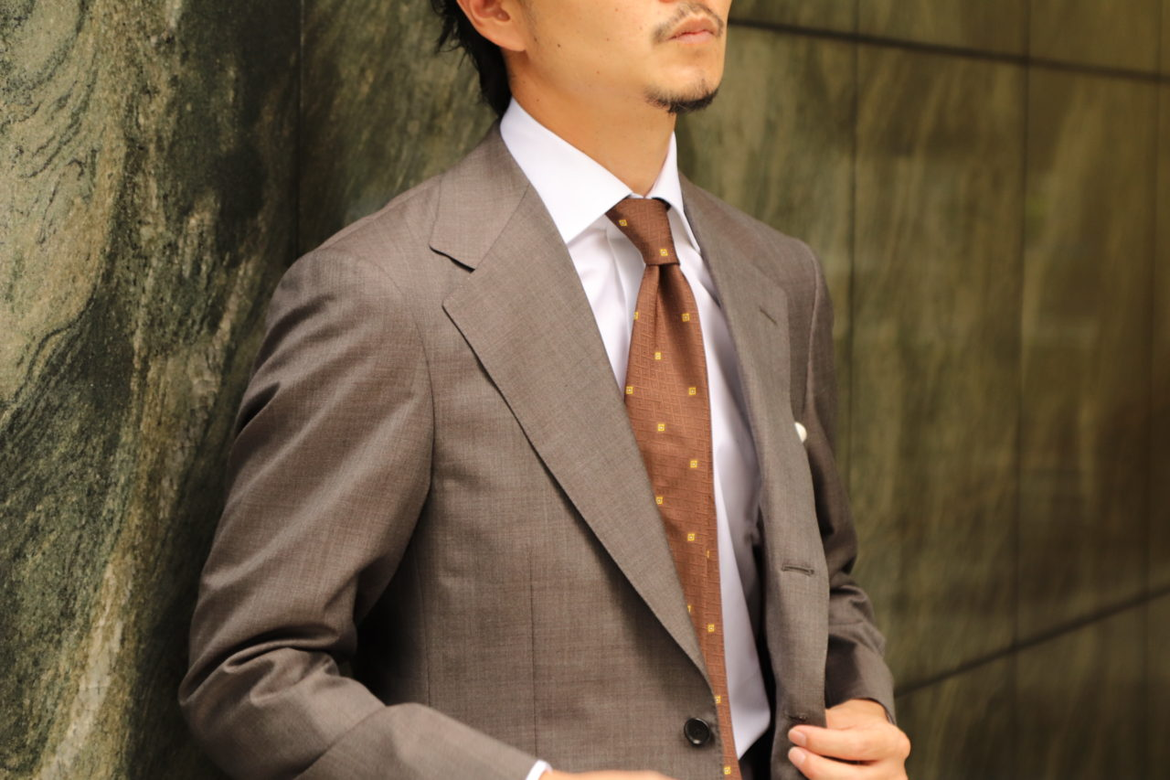 アット ヴァンヌッチ(Atto Vannucci)のブラウンのセッテピエゲネクタイをザ・ジーズ・ハイドアウト(THE G'S HIDEOUT.)のグレーのオーダースーツに合わせたスタイルのご紹介。