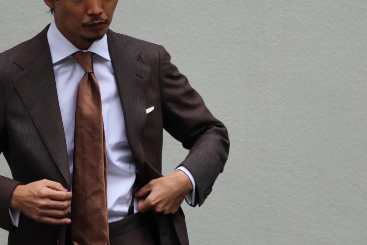 アット ヴァンヌッチ(Atto Vannucci)のブラウンのセッテピエゲネクタイをザ・ジーズ・ハイドアウト(THE G'S HIDEOUT.)のブラウンのオーダースーツに合わせたスタイルのご紹介。