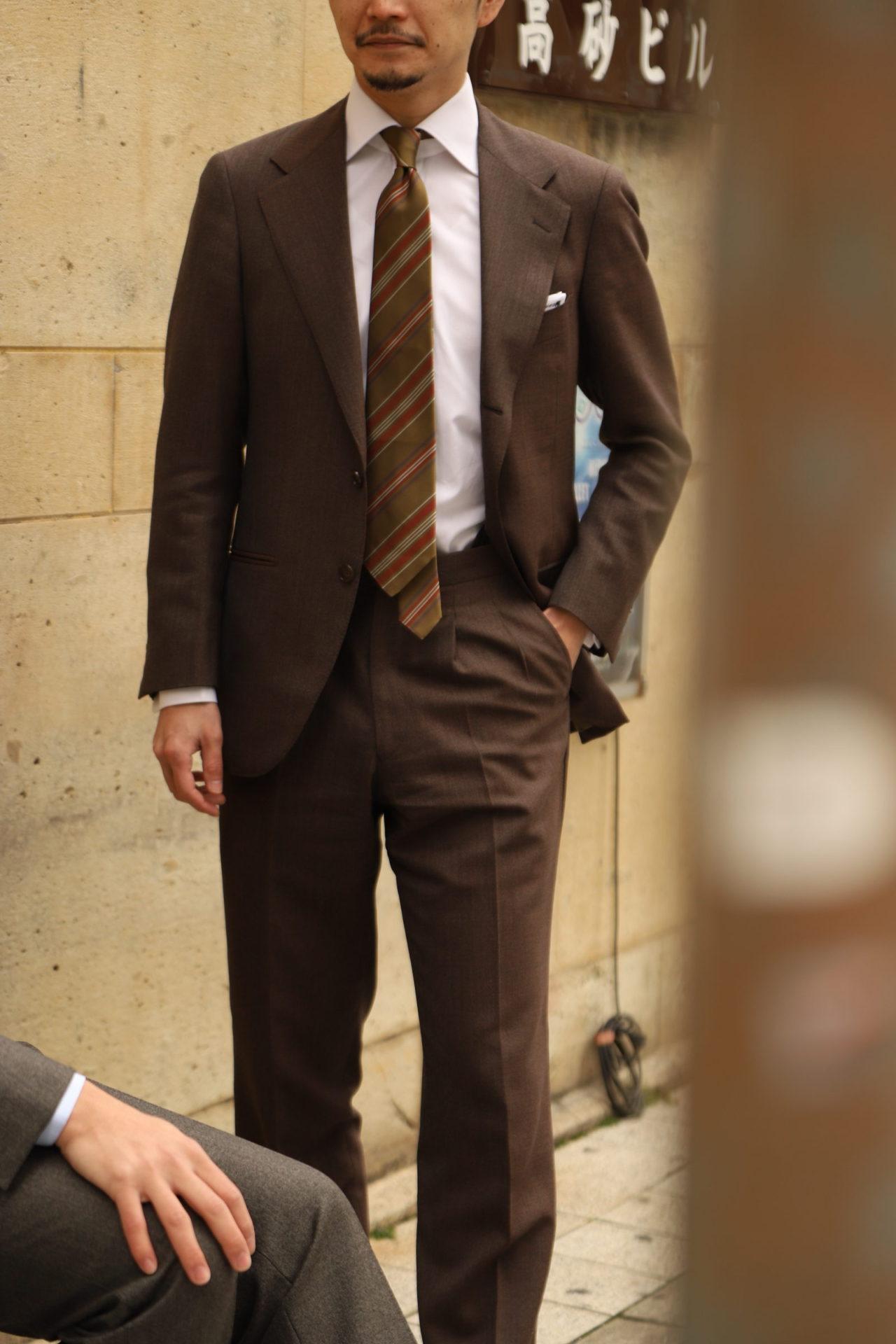 アット ヴァンヌッチ(Atto Vannucci)のグリーンのネクタイをザ・ジーズ・ハイドアウト(THE G'S HIDEOUT.)のレダの生地で仕立てたブラウンオーダースーツに合わせたスタイル。