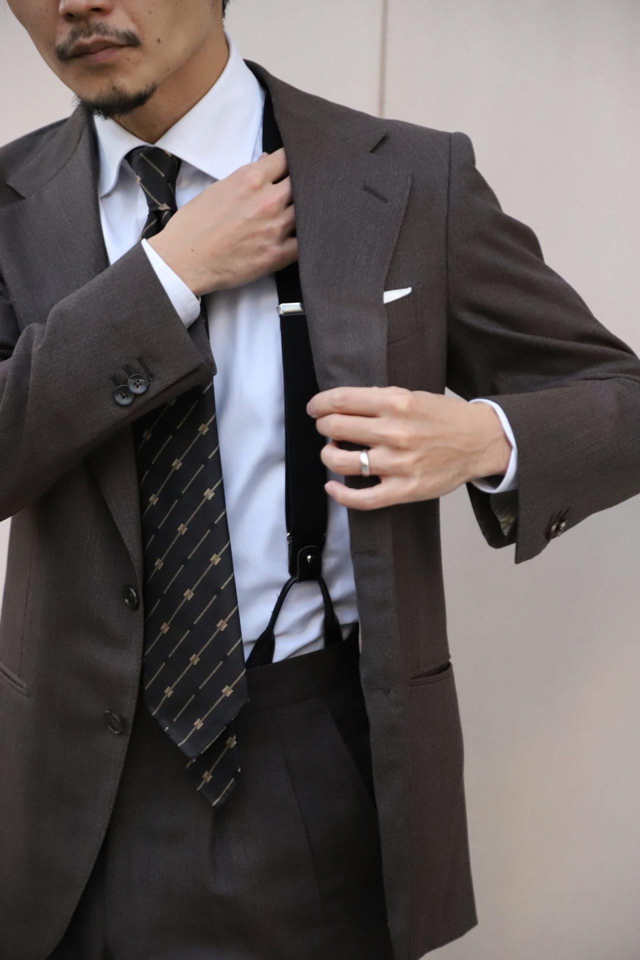 アット ヴァンヌッチ(Atto Vannucci)のブラックのセッテピエゲのネクタイをザ・ジーズ・ハイドアウト(THE G'S HIDEOUT.)のブラウンオーダースーツに合わせたスタイルは都会的で洗練された印象になります。